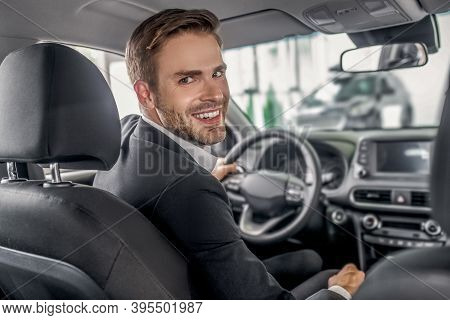 Young Male Sitting At Drivers Seat, Holding Steering Wheel