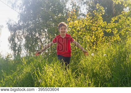 A 10-year-old European Boy In A Red T-shirt Runs Through The Tall Grass. Happy Child In Summer Or Sp