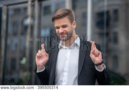Young Businessman Looking Anticipating Keeping Fingers Crossed