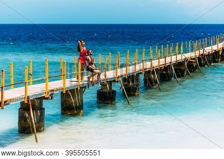 Happy Couple On Vacation Strolling Along A Wooden Pier Above The Tropical Blue Ocean. Beautiful Coup
