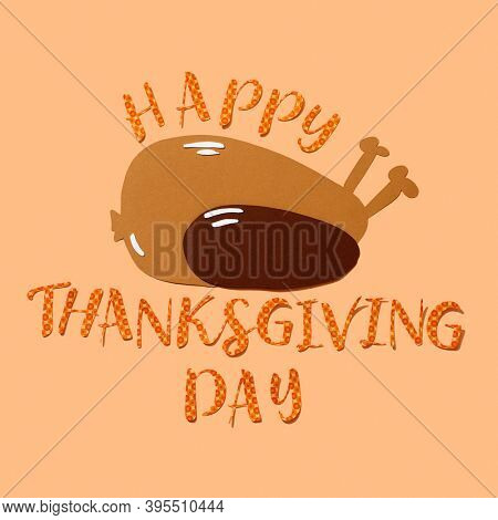a paper cutout in the shape of a roast turkey and the text happy thanksgiving day cutout in a geometric-patterned paper, on an orange background