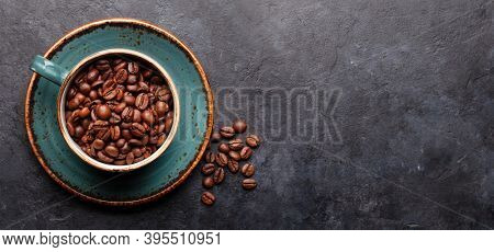 Coffee cup with roasted coffee beans on wide stone table. Top view flat lay with copy space