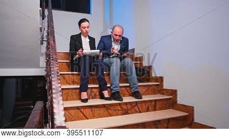 Tired Overworked Businesswoman Arguing With Colleague During Difficult Deadline Sitting On Staircase