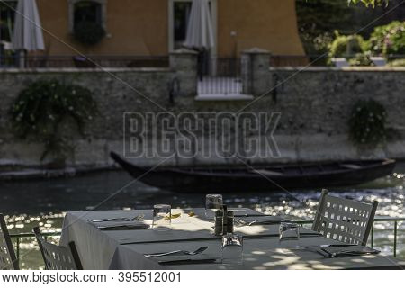 Terrace With Table For Dining On The Mincio River In Borghetto, Verona (italy). Wooden Rowing Boat B