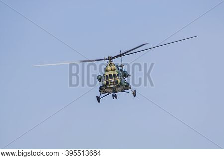 A Military Helicopter Painted In Camouflage Color Is Flying High In The Sky. Close Up.