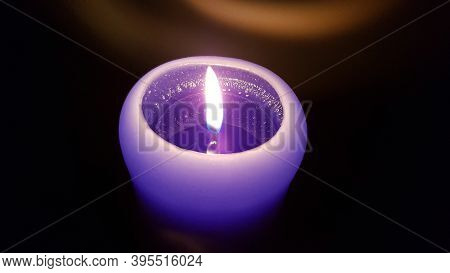 Shiny Candlelight Flame Closeup. Burning Fire Of Purple Candle In Darkness. Reflection Of Glowing Fl