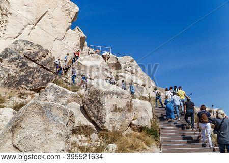 Uchisar, Turkey - October 4, 2020: Unidentified People Climb A Tuff Rock (uchisar Castle), Cut By Ca