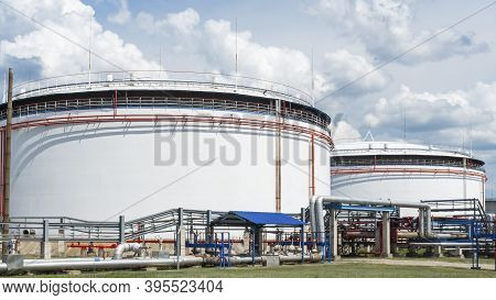 Oil Depot Storage Tanks. Large White Industrial Tanks For Petrol And Oil On Dramatic Sky Background.
