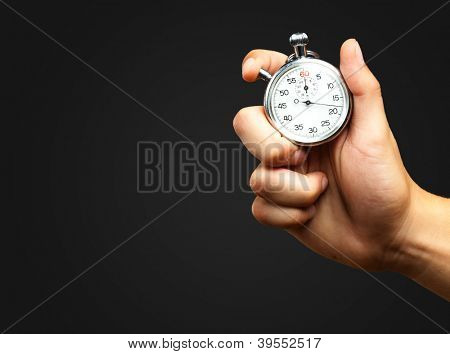 Close Up Of Hand Holding Stopwatch against a black background