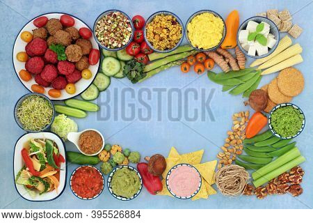 Healthy lifestyle vegan food for good health with bean curd, tofu balls, vegetables, snacks, nuts, dips, cereal & grain products. Health foods that lower cholesterol & blood pressure. On mottled blue.