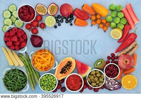 Low carb healthy diet food with fruit & vegetables high in dietary fibre, antioxidants, anthocyanins, vitamins, minerals, carotenoids, smart carbs & protein. Flat lay, top view on mottled blue border.