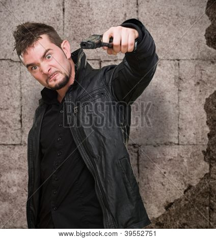 furious man pointing with a gun against an old rusty wall