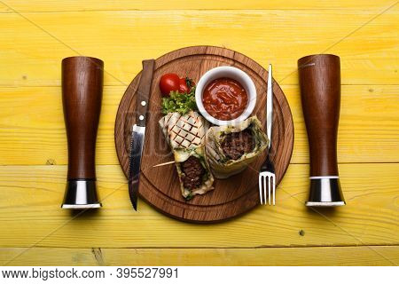 Minced Meat Wrapped With Lavash Bread On Yellow Wooden Background