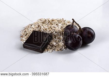 Raw Oatmeal On An Isolated On White Background. Side View Of Raw Dry Rolled Oatmeal With Grapes And