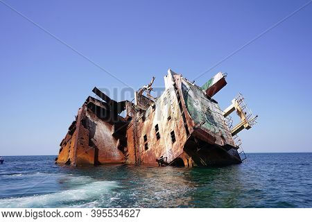 View Of The Shipwreck. The Ship Ran Aground The Side View. Abandoned Sea Vessels. Turquoise Water.