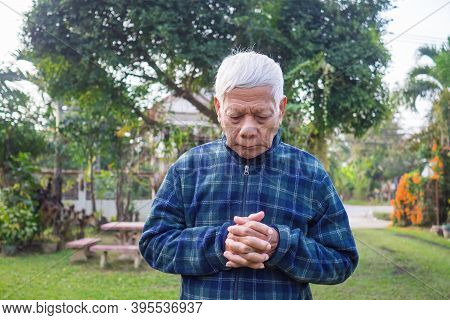 Portrait Of Senior Man Closed His Eyes And Praying While Standing In A Garden. Concept Of Aged Peopl