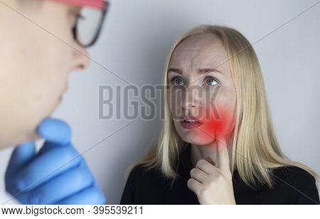 A Woman Clings To His Cheek And Winces In Pain In His Tooth. The Concept Of Dental Problems, Caries,