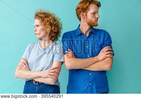 Redhead resentful couple having argument while posing with arms crossed isolated over blue background