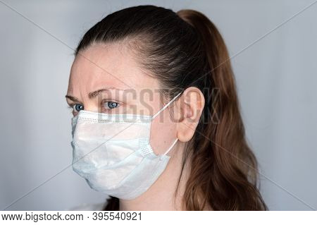 Young Woman Demonstrates Hot To Properly Wear A Face Mask Covering Mouth, Nose And Chin, To Prevent
