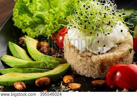 Couscous With A Poached Egg, A Sliced Avocado, A Cucumber, Tomatoes And Lettuce. Served Wih Seasonin