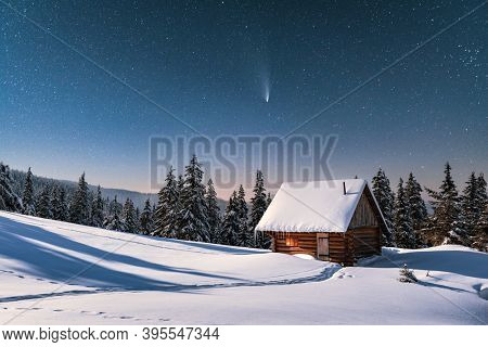 Fantastic winter landscape with wooden house in snowy mountains. Starry sky with comet and snow covered hut. Christmas holiday and winter vacations concept