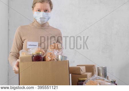 Female Volunteer Working In Food Bank Warehouse. Woman Is Sorting Food. Helping Poor And Needy Peopl