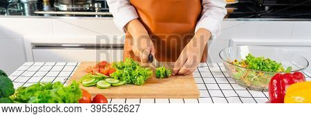 Young Asian Woman Is Preparing Healthy Food Vegetable Salad By Cutting Ingredients On Cutting Board