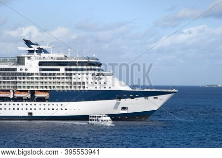 The Morning View Of A Tender Boat Taking Passengers From The Giant Cruise Liner To Grand Cayman Isla