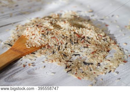 Rice Mixture Of Different Varieties Scattered On A White Wooden Table. A Wooden Loo For Pouring Rice