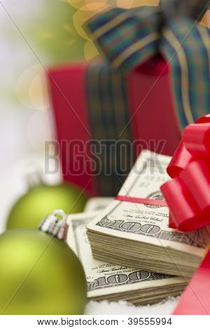 Stack of One Hundred Dollar Bills with Red Bow Near Green Christmas Ornaments and Wrapped Gift Box on Snow Flakes.