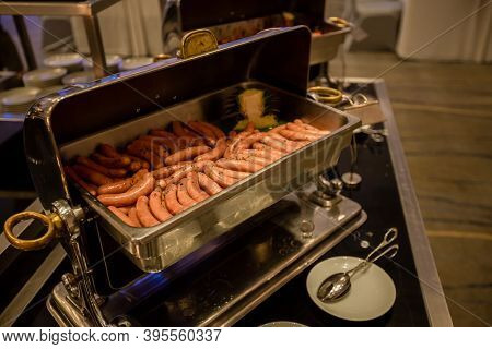 Breakfast Sausage Or Hot Dog Cooking In Buffet Food Warmer. Self-service Buffet Table. Celebration,