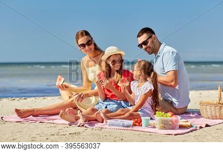 family, leisure and people concept - happy mother, father and two daughters having picnic on summer beach and eating watermelon