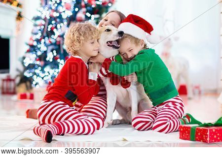 Christmas At Home. Kids And Dog Under Xmas Tree. Little Boy And Girl Hug Pet In Santa Hat And Open C