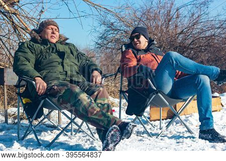 Two Young Men Rest On Camping Chairs In Campside At Sunny Day, Friends Relax In Wild, Winter Lifesty