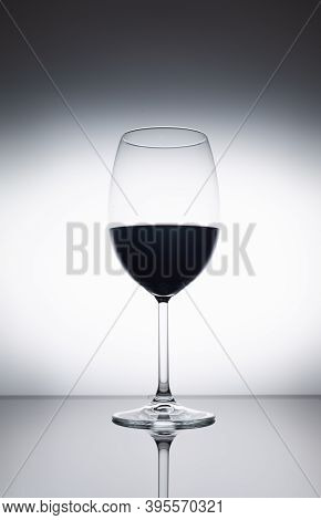 Red Wine In Glas. Glass With Red Wine On Black Glass On White Background Close-up
