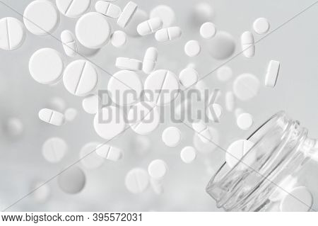 White Medical Pills Flying Out Of A Glass Jar