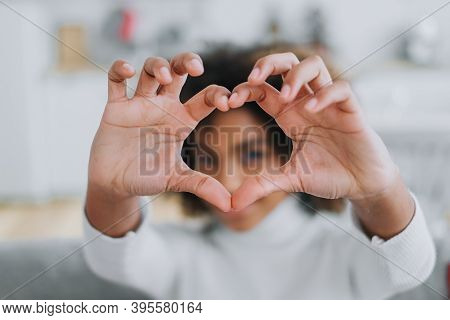 Cheerful Dark Skinned Lady With Kinky Hair Holds Fingers In Heart Shape And Showing To Camera Smilin