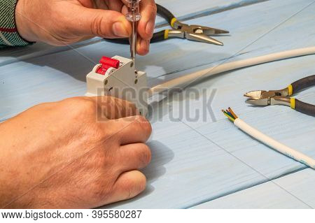 Master Electrician Connects Electrical Cable And Circuit Breaker With Screwdriver