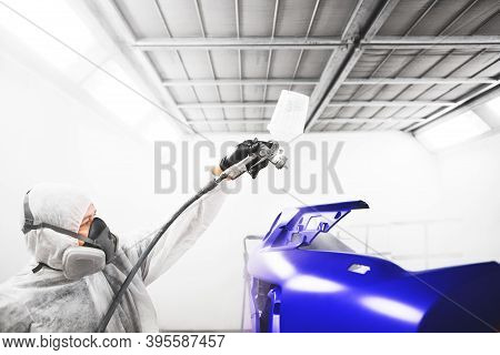 Male Worker Sprays Varnish With Spray Gun On Car Element After Painting.