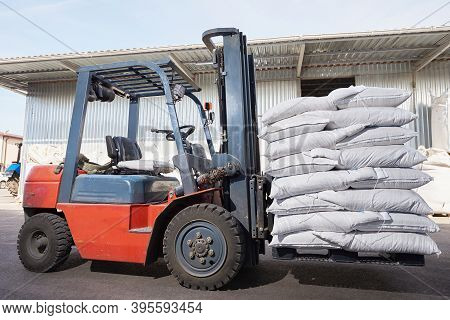 Red Forklift Lifts Pallet With White Bags