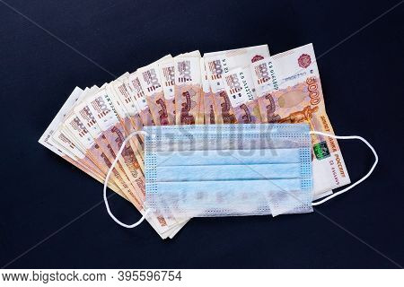 Russian Money, Rubles Wrapped In A Medical Mask. Medical Face Masks And Money. Surgical Face Mask. C