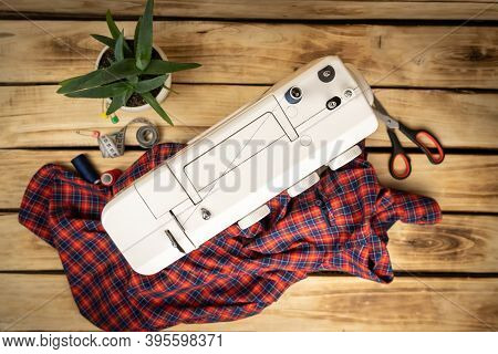 White Sewing Machine, Which Sews A Plaid Mens Shirt. Cutting And Sewing Concept. Womens Hobby