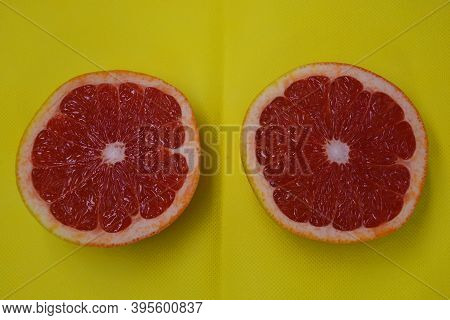 Ripe And Tasty Fruits, Fresh Grapefruit Cut In Half, Sliced Grapefruit Set On A Yellow Fabric Backgr