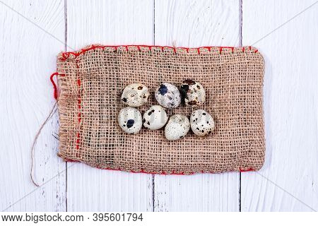 Quail Eggs On Burlap Cloth Bag. Group Of Quail Eggs Close-up. Top View. Detailed Closeup Of Spotted