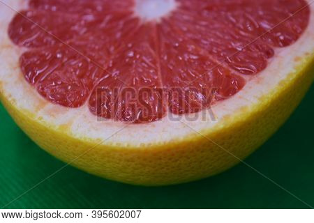 Ripe And Tasty Fruits, Fresh Grapefruit Cut In Half, Sliced Grapefruit Set On A Green Fabric Backgro