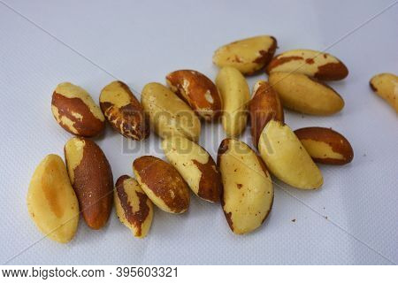 Bright And Tasty, Brown And White Brazil Nuts (bertholletia Excelsa) Are Arranged On A Matte White B