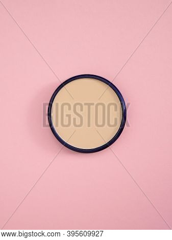 Beige Facial Concealer Powder. Top View Of Nude Face Powder In Round Case On Pink Paper Background.