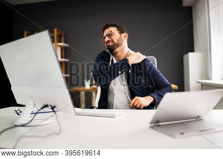Young Man With Tense Shoulder Pain. Office Posture Problem