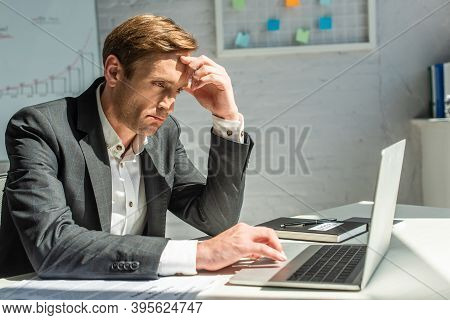 Upset Businessman Using Laptop, While Sitting Near Petitions For Bankruptcy On Table With Blurred Of