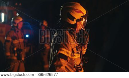 Close Up Of Firefighter Using Radio To Speak With His Collegues. Fire Engine With Emergency Lights A